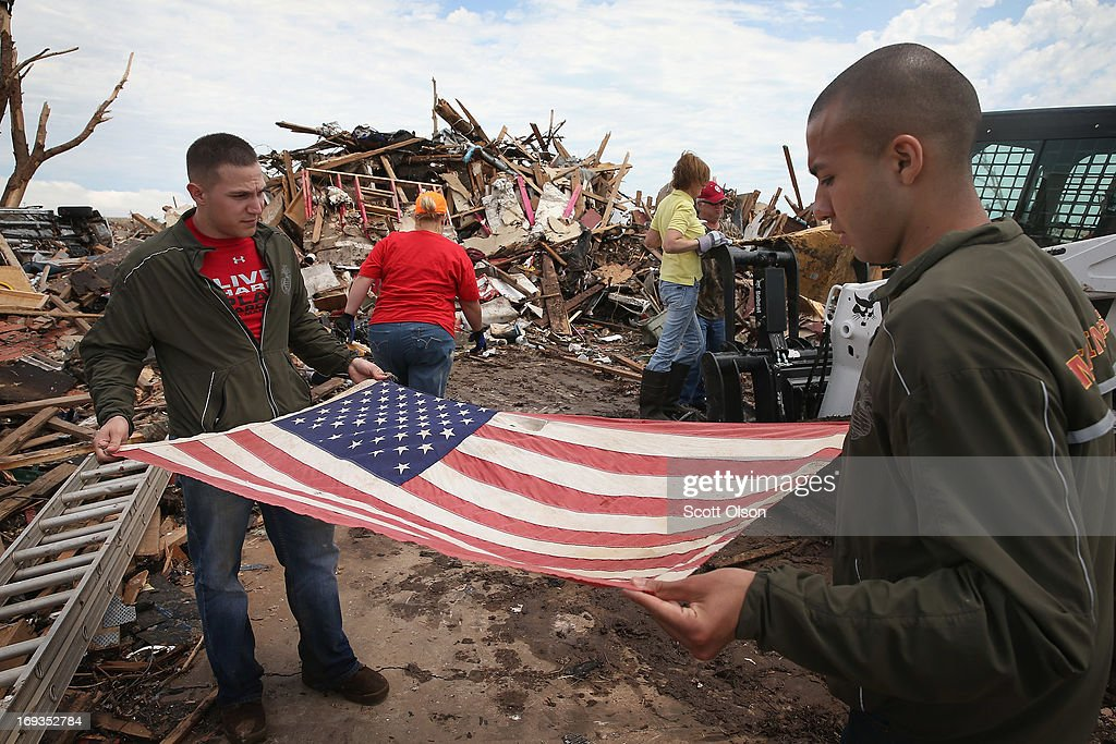 U.S. Marines Cpl. Dylan Rhodes (L) of Owasso, Oklahoma and Cpl. Patrick Canales of Los Angeles, California fold a flag for Tim Jones and Christine Jones that had been flying from a tree in front of their home, after it was destroyed by a tornado, May 23, 2013 in Moore, Oklahoma. The flag would hang outside the Jones' home on national holidays. On Monday May 20 It was hung in a tree outside of the home after the family returned home to find their house had been leveled by a tornado and the flag tangled in the garage rafters. Today, with the help of the Marines, they decided to preserve the flag. A two-mile wide EF5 tornado touched down in Moore May 20 killing at least 24 people and leaving behind extensive damage to homes and businesses. U.S. President Barack Obama promised federal aid to supplement state and local recovery efforts.