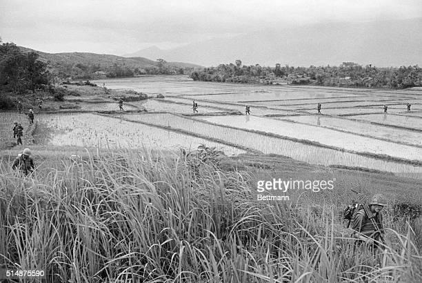 US marines cross a flooded rice paddy in Da Nang Vietnam during the Vietnam War