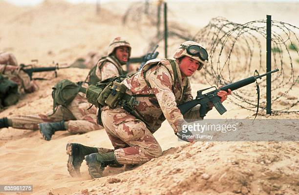 US Marines crouch behind a barrier of barbed wire They are training in a Saudi Arabian desert just before the onset of the Gulf War