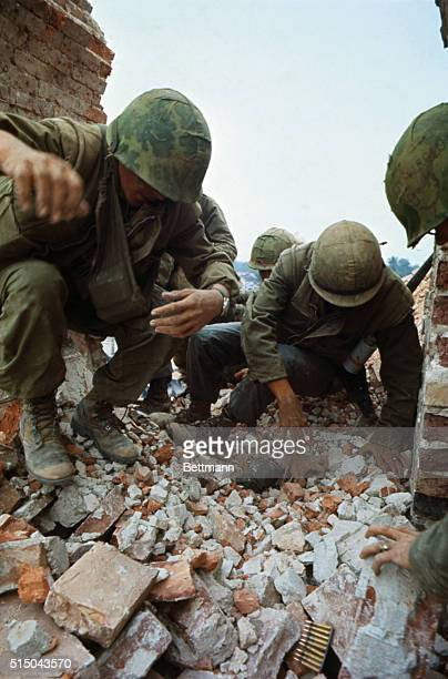 US Marines dig with their hands through brick rubble burying PFC Thomas A Zwetow who was standing on a tower of the citadel when it was hit by...