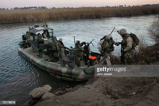 S Marines disembark from their boat to look for insurgent arms cashes on the bank of the Euphrates River February 2 2007 in Ramadi Anbar Pronvince...