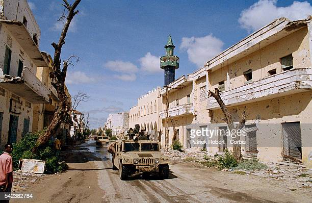 Marines drive past damaged buildings while stationed in Somalia for Operation Restore Hope, the codeword for the American military mission protecting...