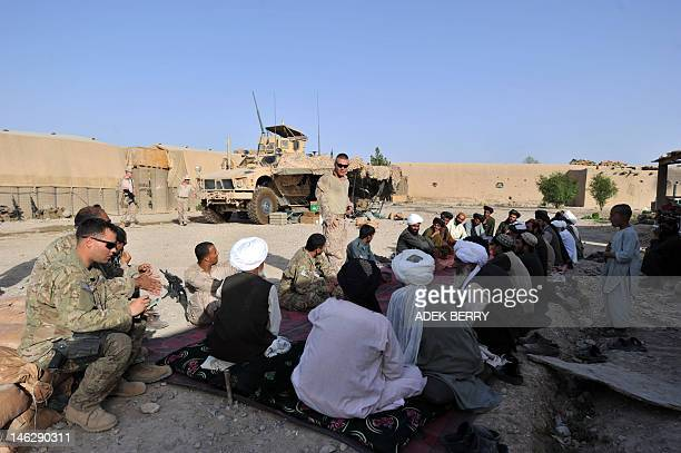 US Marines from 1st Battalion 7th Marines Regiment hold a shura meeting with local police and residents at PB Fulod in Sangin on June 12 2012 The...