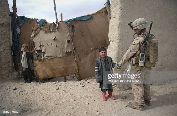 Marines from 1st Battalion 8th Marines shakes hands with children during a patrol outside Musa Qala District Center base on January 28 2011 Taliban...