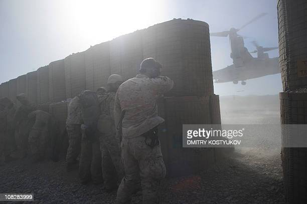 US Marines from 1st Battalion 8th Marines shield themselves as a V22 Osprey tiltrotor aircraft kicks up dust while landing at the Musa Qala District...