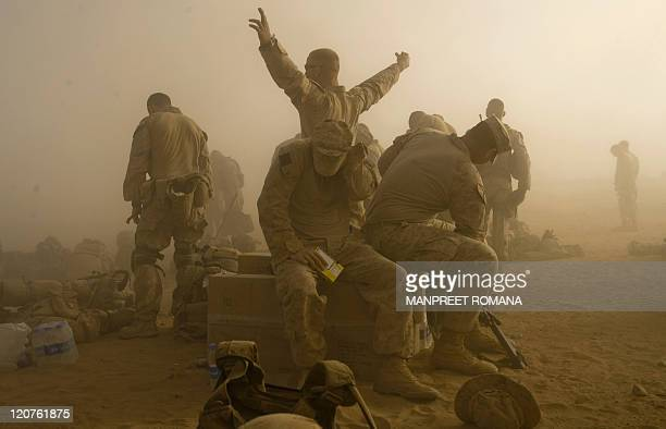US Marines from 2nd Battalion 8 Marine Regiment of 2nd Marine Expeditionary Brigade shield themselves from dust blown up by helicopters as they leave...