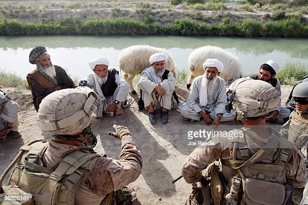 S Marines from 2nd Marine Expeditionary Brigade RCT 2nd Battalion 8th Marines Echo Co meet with Afghan villagers who returned after the Marines drove...