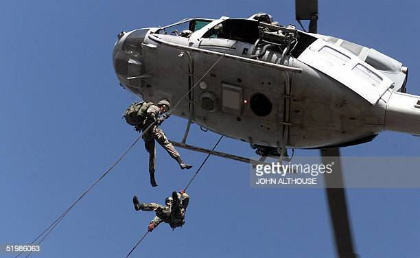 Marines from 4th Marine Expeditionary Brigade rappel from a UH1 Heuy helicopter during exercises 08 November 2001 at Camp Davis NC The 4thMEB...
