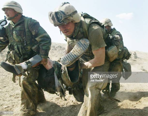 Marines from Task Force Tarawa carry a wounded Marine during a gun battle March 23, 2003 in the southern Iraqi city of Nasiriyah. The Marines...