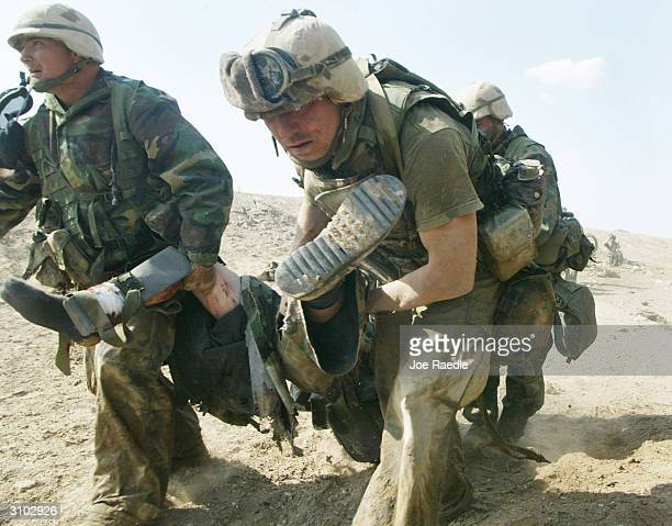 S Marines from Task Force Tarawa carry a wounded Marine during a gun battle March 23 2003 in the southern Iraqi city of Nasiriyah The Marines...