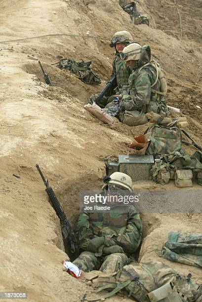 Marines from Task Force Tarawa prepare in their muddy fox holes after a rainy night March 26, 2003 in the southern Iraqi city of Nasiriyah. As night...