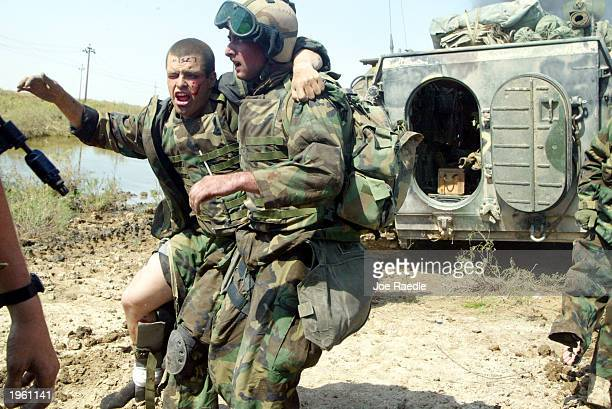 Marines from Task Force Tarawa take care of their wounded while being pinned down by intense enemy fire March 23, 2003 in the southern Iraqi city of...