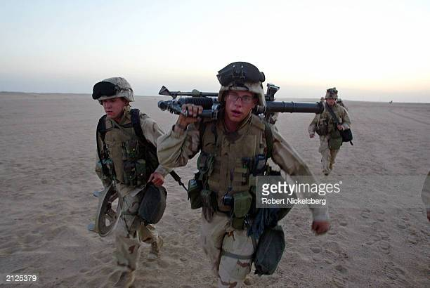 Marines from the 1st Marine Division, 7th Regiment, sweat through an early morning five mile run March 14, 2003 at Life Support Area 7 , in the...