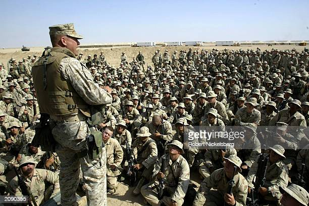 Marines from the 1st Marine Division listen to their battalion commander, Lt. Col.Bryan McCoy, March 18, 2003 45 km south of the Iraqi border in the...