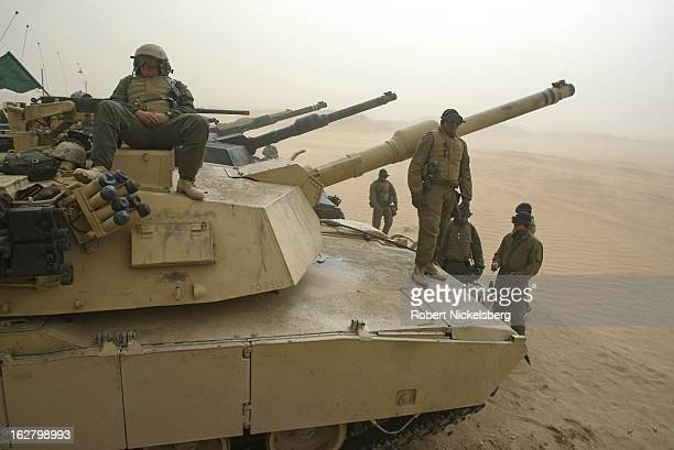 S Marines from the 1st Marine Division rest on top of their M1A1 Abrams tanks February 3 2003 during a sandstorm waiting for sighting in exercises to...
