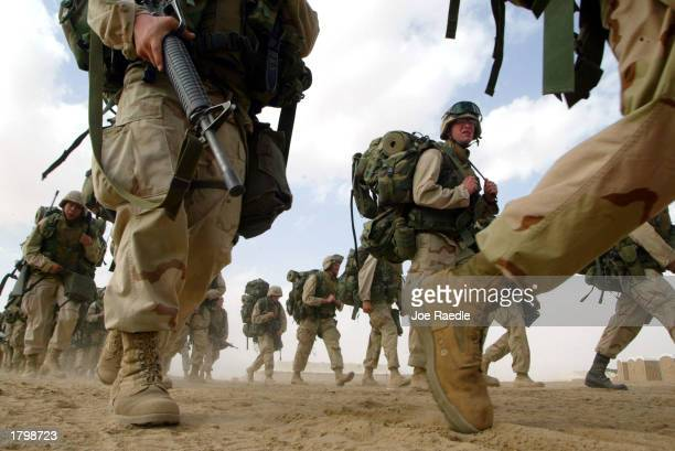 Marines from the 1st Marine Division return from a six-mile march February 15, 2003 near the Iraqi border in Kuwait. The Marines continue to prepare...