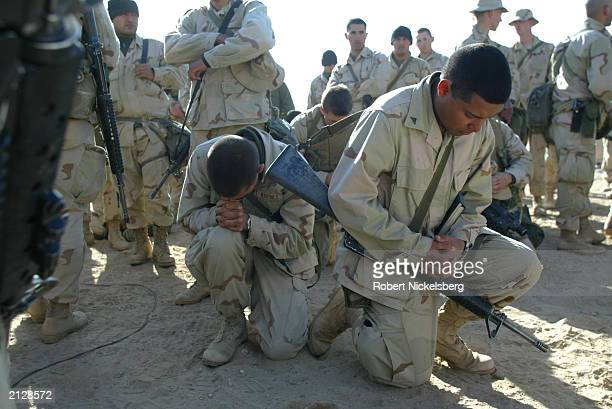 Marines from the 1st Marine Divison pray following a Sunday Catholic mass February 23, 2003 in Kuwait at Life Support Area 7 . LSA 7 is the...