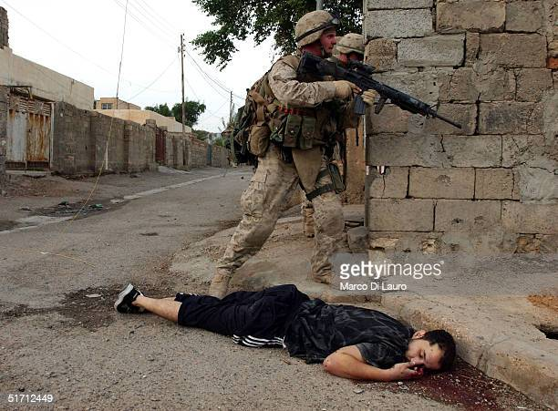 S Marines from the 1st US Marines Expeditionary Force 1st Battalion 3rd Marines Regiment Bravo Company pass by a dead body of a suspected insurgent...