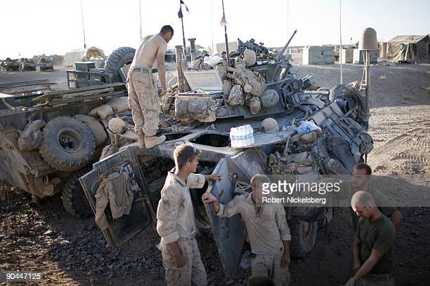 Marines from the 2nd Marine Division 2nd Light Armored Reconnaissance Battalion cool off at sunset outside their Light Armored Vehicles in the...