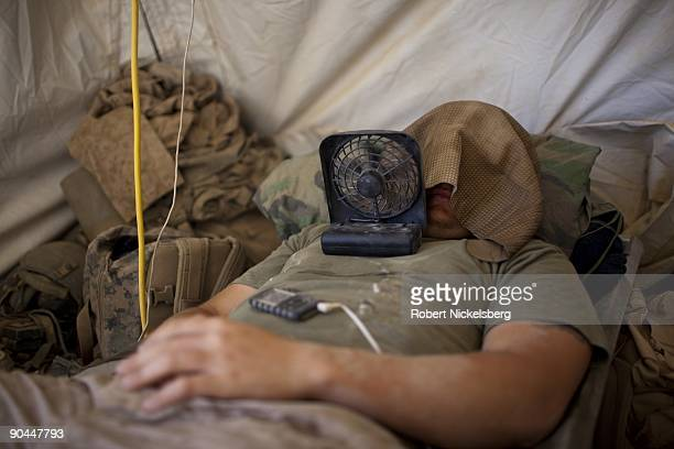 Marines from the 2nd Marine Division 2nd Light Armored Reconnaissance Battalion Charlie Company use fans and wet cloths to cool off during midday...