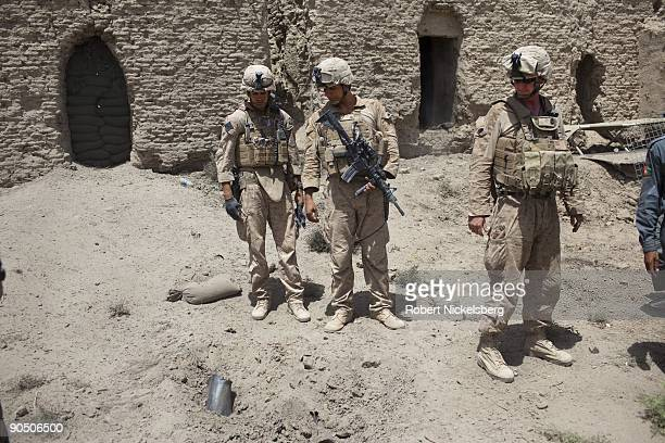 Marines from the 2nd Marine Division 2nd Light Armored Reconnaissance Battalion Delta Company check the impact point of a Talibanfired 107mm rocket...