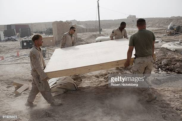 Marines from the 2nd Marine Division 2nd Light Armored Reconnaissance Battalion Delta Company unload wooden floorboards for a shower room at Forward...