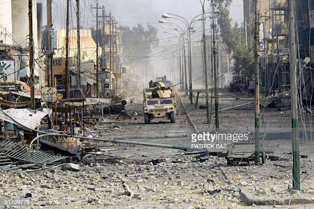 US marines from the 3/5 Lima company ride in their Humvees along the main high street of the restive city of Fallujah 14 November 2004 50 kms west of...