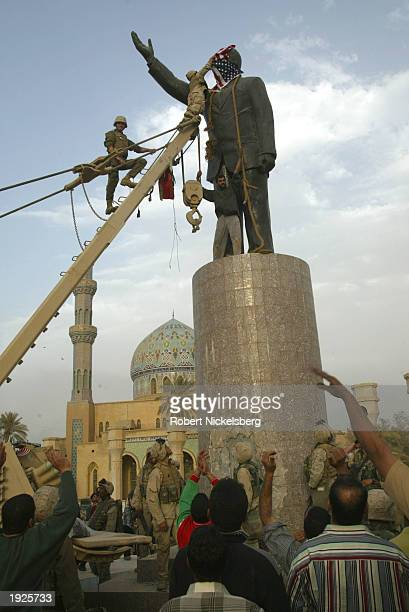 US Marines from the Marine 1st Division help Iraqi civilians topple a Saddam Hussein statue near the Palestine Hotel April 9 2003 in Baghdad Iraq...