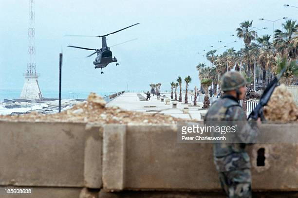 Marines guard the evactuation of American European and other foreign civilians who are being ferried by US military helicopters to ships off the...