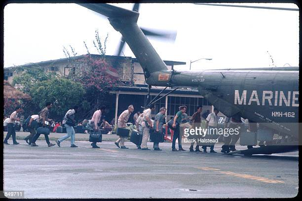 Marines guard the evacuation of civilians at Tan Son Nhut airbase in Vietnam while under Viet Cong fire, during the fall of Saigon, April 15, 1975.