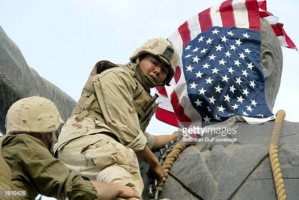 US Marines hang the Stars and Stripes on a statue of Saddam Hussein before helping the citizens of Baghdad pull it down