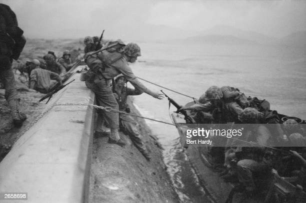 US Marines land from assault craft and climb over the sea defences at Inchon in South Korea during the Korean War after heavy bombardment of coastal...