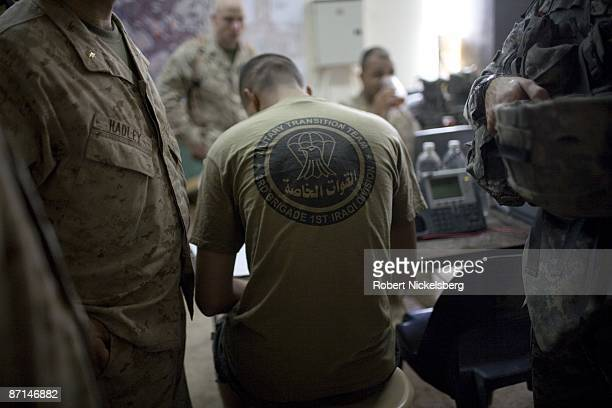 Marines left and center talk over forward movements of their Iraqi Army units they liaison with for training and guidance inside an Iraqi Army...