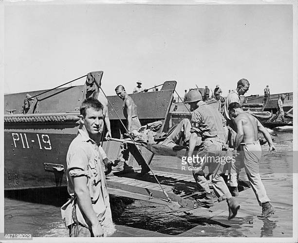 US Marines loading equipment onto landing craft vehicles as they prepare to leave Guadalcanal during World War Two Solomon Islands circa 19441945