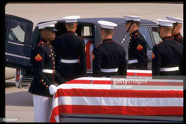 Marines loading flag-draped coffins of US Marines slain by Salvadoran rebels flown home for burial into hearse, at Andrews AFB mil. Ceremony.