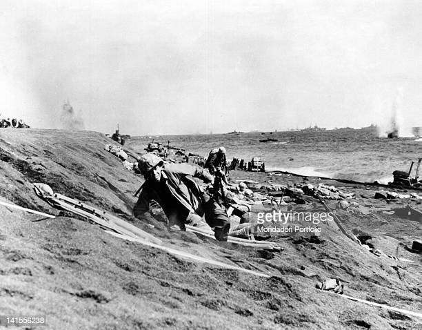 US Marines lying on the beach of Iwo Jima bombarded by Japanese artillery Iwo Jima February 1945