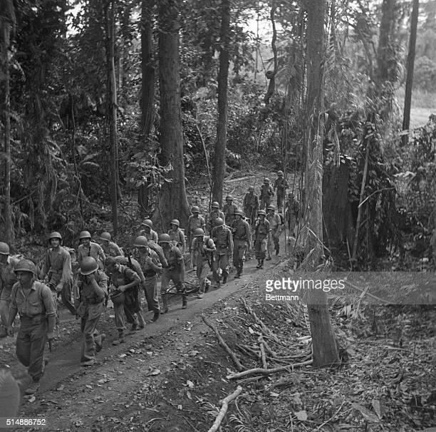 Marines march through tropical jungles on Guadalcanal, getting into position for their attack on Japs entrenched on the Matanikou River.