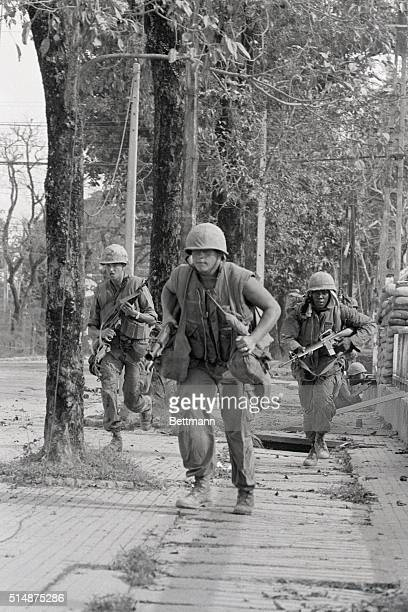 US marines move down a street in Hue South Vietnam during the Vietnam War