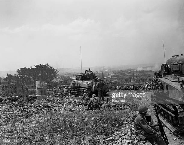 Marines move into Naha, capital city of Okinawa, Ryukyu Islands in the face of stiff Japanese resistance. The men are on a hill overlooking the city,...