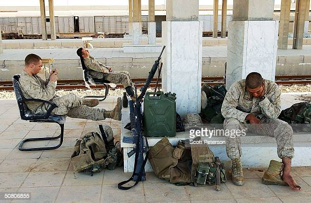 Marines of 2nd Battalion 1st Marine Regiment rest after keeping watch overnight as they maintain their cordon at the key flashpoint Fallujah railway...