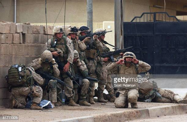 S Marines of Bravo Company 1st Battalion 3rd Marines listen for an explosive charge to open a doorway as they make their final attack completing a...