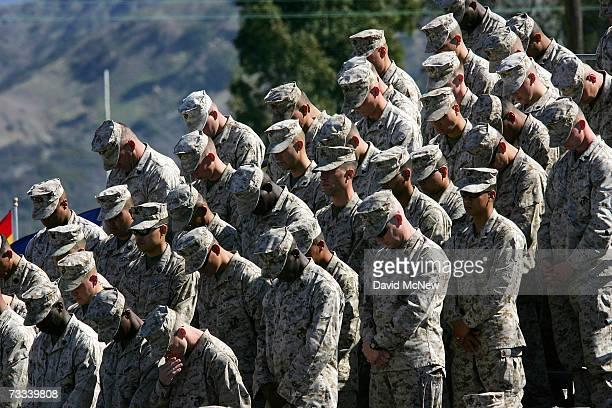 Marines of Regimental Combat Team 5 bow their heads in prayer as they memorialize 100 Marines soldiers and sailors who died during the regiment's...