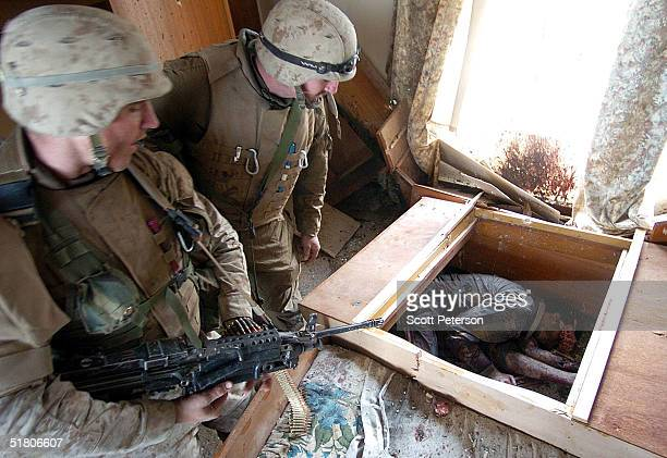 Marines of the 1st Battalion 3rd Marines check a body after a battle with three insurgents while searching a house which left one marine dead and...