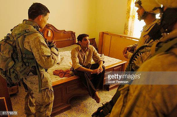 Marines of the 1st Light Armored Reconnaissance company as part of 1st Battalion 3rd Marines question a man found in a house as they search for...