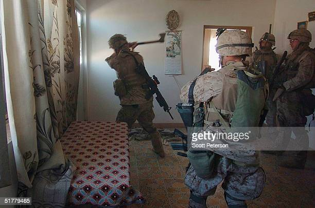 Marines of the 1st Light Armored Reconnaissance company as part of 1st Battalion 3rd Marines use an axe to open a door as they search houses for...