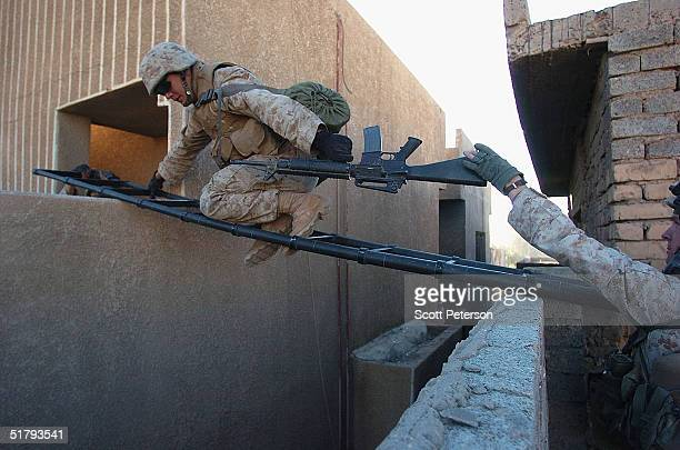 Marines of the 1st Light Armored Reconnaissance company as part of 1st Battalion 3rd Marines use a breach ladder to cross from rooftop to rooftop as...
