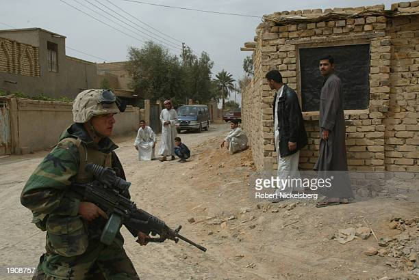 Marines of the 1st Marine Division move past Iraqi civilians March 30, 2003 in Tahrir, Iraq, which is approximately 100 km south of Baghdad....