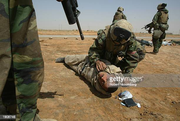 Marines of the 1st Marine Division secure a POW April 1, 2003 in Diwaniya, Iraq. Diwaniya, a city of 300,000 residents, where the 1991 Shiite...