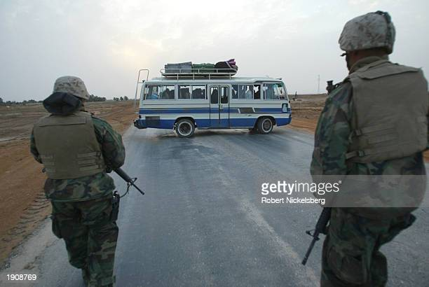 Marines of the 1st Marine Division turn around a civilian bus of Iraqis March 30, 2003 as a Marine convoy moves out of Tahrir, a city Marines had...