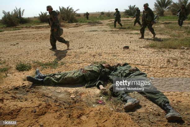 US Marines of the 1st Marine Division walk past two dead Iraqi Army soldiers April 1 2003 in Diwaniya Iraq Diwaniya a city of 300000 residents where...